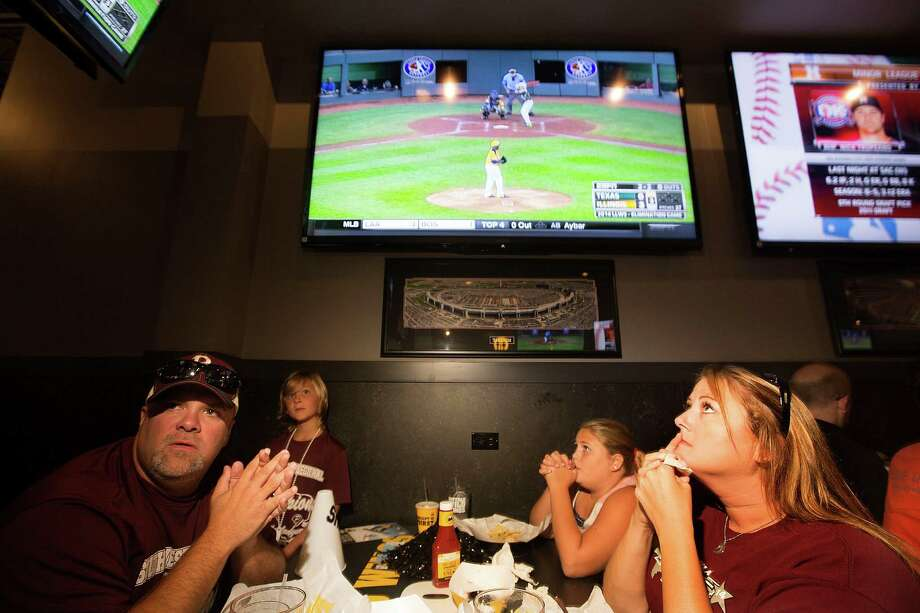 Stephen Borden, his wife, Vige and children, Cash, 8, and Bayleigh, 11, react while watching Pearland East play Chicago's Jackie Robinson West in the Little League World Series broadcast at Buffalo Wild Wings Tuesday, Aug. 19, 2014, in Pearland. Photo: Johnny Hanson, Houston Chronicle / © 2014  Houston Chronicle