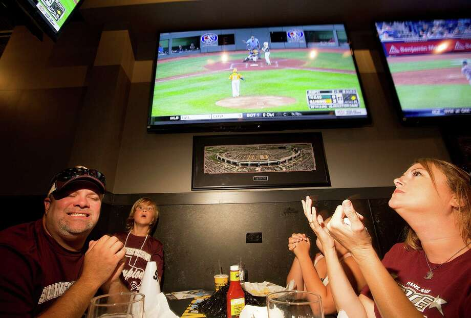 Stephen Borden, his wife, Vige and children, Cash, 8, and Bayleigh, 11, react to a play while watching Pearland East play Chicago's Jackie Robinson West in the Little League World Series broadcast at Buffalo Wild Wings Tuesday, Aug. 19, 2014, in Pearland. Photo: Johnny Hanson, Houston Chronicle / © 2014  Houston Chronicle