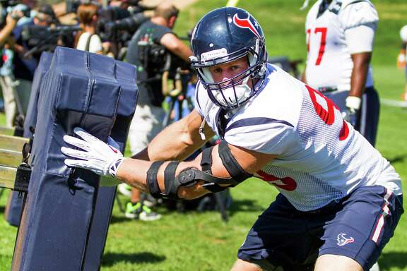 Houston Texans defensive end J.J. Watt (99) hits a blocking sled during a joint practice with the Denver Broncos at the Broncos training facility on Tuesday, Aug. 19, 2014, in Englewood, Colo. ( Brett Coomer / Houston Chronicle )