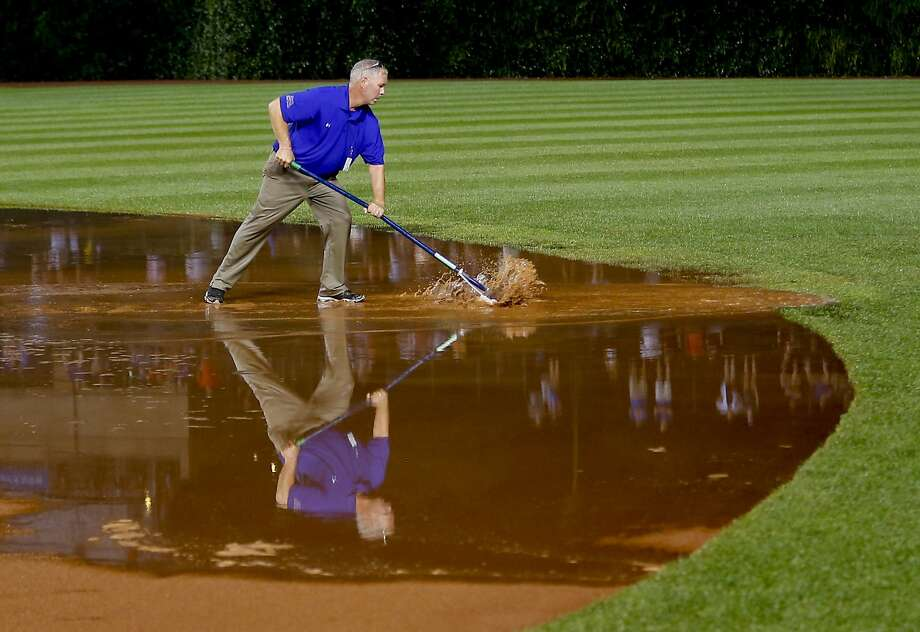 A member of the grounds crew works on the field after a heavy rain soaked Wrigley Field during the fifth inning of a baseball game between the San Francisco Giants and the Chicago Cubs on Tuesday, Aug. 19, 2014, in Chicago. Photo: Jeff Haynes, Associated Press
