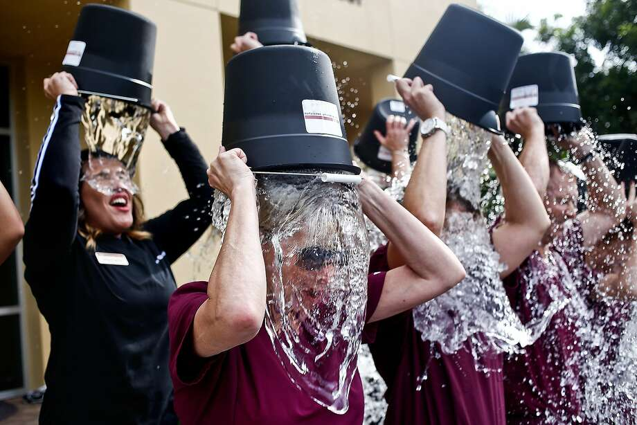 Debbie Wallace, center, dumps a bucket of ice water on her head along with her coworkers as they participate in an Ice Bucket Challenge at the Woodruff Institute in Naples, FL on Tuesday, August 19, 2014. Wallace, a physician assistant at Woodruff, lost her brother Chester to ALS two weeks before and challenged her coworkers in the challenge. The Ice Bucket challenge began on social media on July 29 to benefit ALS or amyotrophic lateral sclerosis. Participants dump a bucket of ice water over their heads, record it and nominate someone else to do the same. If the person nominated doesn't comply or fails to record their video within 24 hours, they must donate cash to benefit ALS research. Between July 29 and Aug. 16, The ALS Association and its 38 chapters have received $11.4 million in donations.   (AP Photo/Naples Daily News, Scott McIntyre)  FORT MYERS OUT Photo: Scott McIntyre, Associated Press