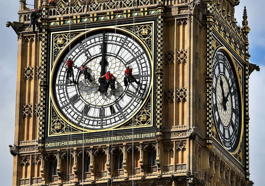 TOPSHOTS Technicians carry out cleaning and maintenance work on one of the faces of the Great Clock atop the landmark Elizabeth Tower that houses Big Ben, attached to the Houses of Parliament, in London, on August 19, 2014. A team of abseilers is busy this week cleaning up the clock faces at the Houses of Parliament in London. The specialist technicians descend the most famous London landmark by rope to clean and inspect the four clock faces. The clock on the Elizabeth Tower was last cleaned in 2010 and besides cleaning up any dirt that has accumulated since then, the experts will conduct a photographic survey to check the dials for damage.  AFP PHOTO / BEN STANSALLBEN STANSALL/AFP/Getty Images Photo: Ben Stansall, AFP/Getty Images