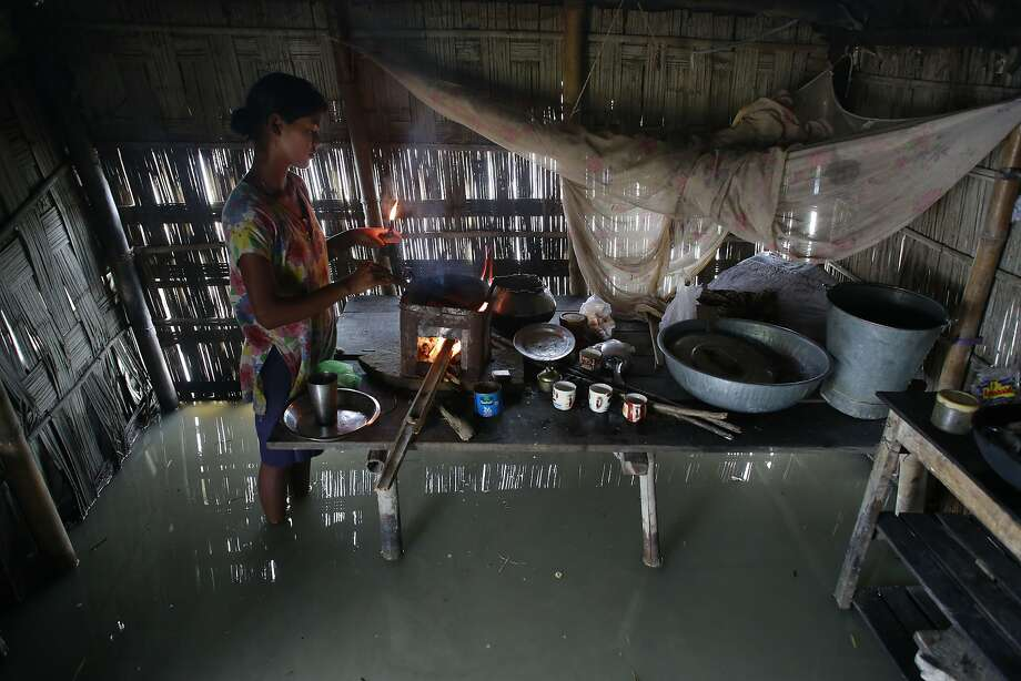 Dupura Akhtar, cooks inside her flood-affected house in Ashigarh village, about 70 kilometers (44 miles) east of Gauhati, India, Thursday, Aug. 19, 2014. Heavy rainfall for the past few days has affected several districts of Assam state, flooding dozens of villages and displacing thousands. (AP Photo/Anupam Nath) Photo: Anupam Nath, Associated Press