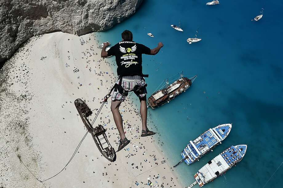 TOPSHOTS Lukas Michul, a member of the 'dream walker' group jumps from atop the rugged rocks overlooking the azure waters of Navagio beach, one of the Greece's most renowned leisure spots on the popular tourist island of Zakynthos on June 23, 2014.  This is rope jumping -- part diving, part rock climbing, with a touch of engineering. The aim of the project is to dream jump in 80 places with most ravishing nature and architecture all over the world .They plan to stage their next leaps at a cave complex in Croatia, a French viaduct, skyscrapers in Las Vegas and Johannesburg, and the Grand Canyon. AFP PHOTO /  LOUISA GOULIAMAKILOUISA GOULIAMAKI/AFP/Getty Images Photo: Louisa Gouliamaki, AFP/Getty Images