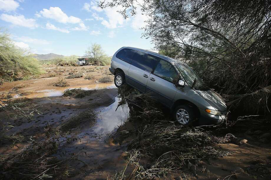 A vehicle sits atop debris where flash flood waters pushed it after rising waters overran Skunk Creek after strong storms moved through, Tuesday, Aug. 19, 2014, in New River, Ariz., just northwest of Phoenix. Heavy monsoon season rains that swept across Arizona on Tuesday led to dramatic rescues, road closures and flight delays as a series of fast-moving storms pummeled the state.  (AP Photo/Ross D. Franklin) Photo: Ross D. Franklin, Associated Press