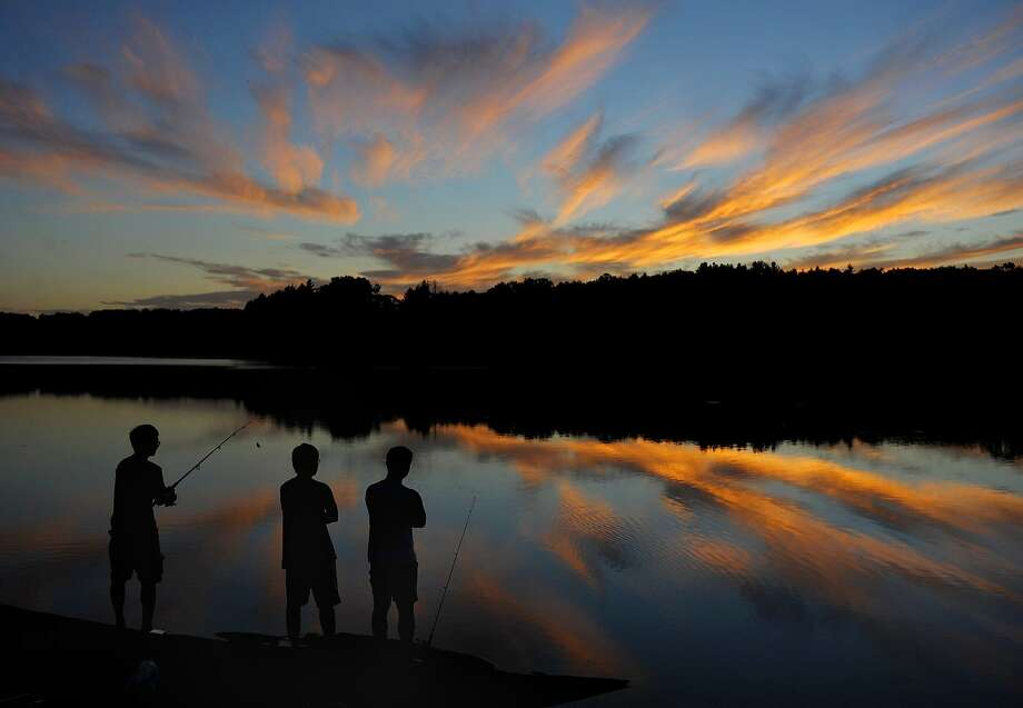 UConn students from Storrs Conn., Gary Tu , Danny Wang and Victor Zheng, stop to admire the sunset set while fishing at Shenipisit Lake, Tuesday evening, Aug, 19, 2014,  in Tolland, Conn. (AP Photo / Journal Inquirer, Jim Michaud) Photo: Jim Michaud, Associated Press