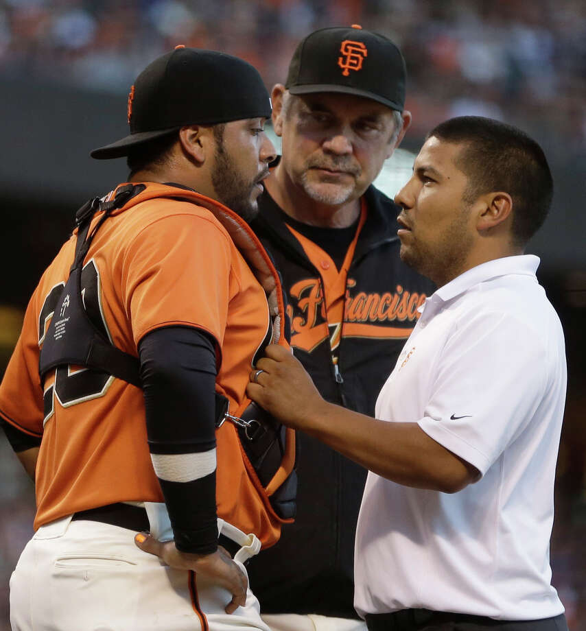 San Francisco Giants manager Bruce Bochy, center, and a trainer check on the condition of catcher Hector Sanchez, left,  in the second inning of a baseball game against the Los Angeles Dodgers on Friday, July 25, 2014, in San Francisco. Sanchez did not return to the game in the third inning. (AP Photo) Photo: Associated Press / AP