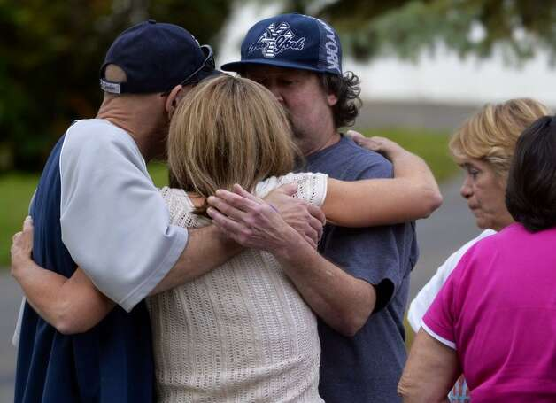 A relative of two people who were found beaten to death inside a home at 709 First Ave., in Troy, are comforted by co-workers of one of the dead. (Skip Dickstein / Times Union)