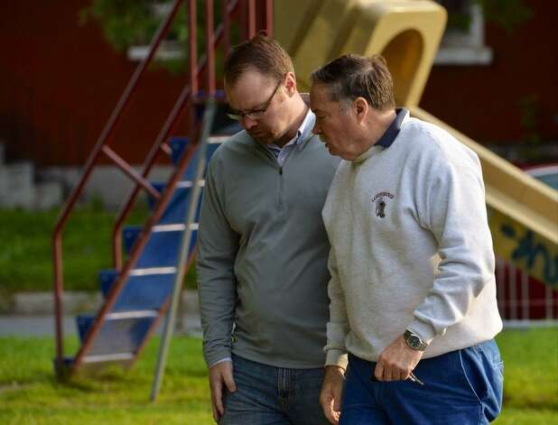 Rensselaer County Assistant District Attorney Shane Hug talks to Bill Reilly, an older brother of Michael Allen Lockrow, who was killed with his wife during a furious attack in their  709 First Ave., Troy home on Wednesday. (Skip Dickstein / Times Union)
