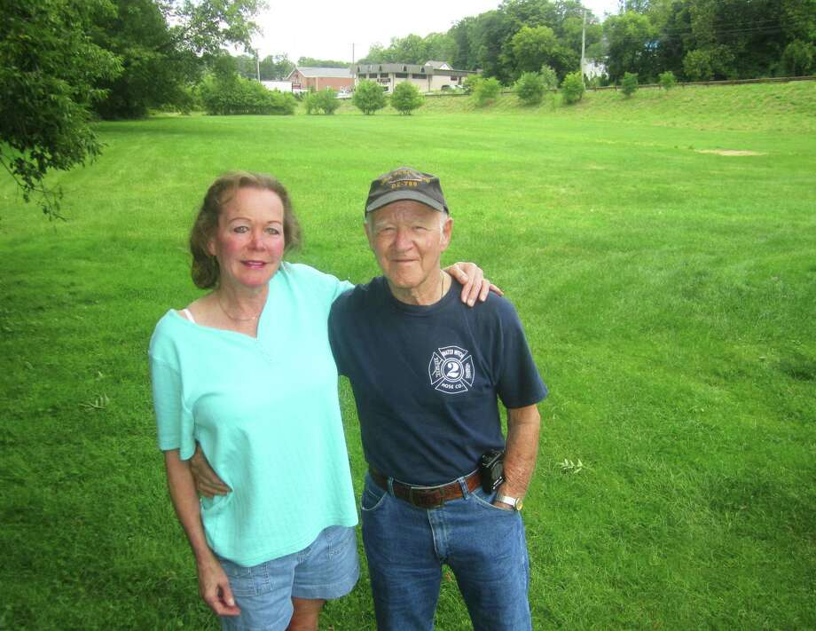Paul Hulton, shown with one of his three daughters, Chrissie Scribner, is offering to donate this property along Grove Street to the town of New Milford as a park in memory of his father, James Hulton. August 2014 Photo: Norm Cummings / The News-Times