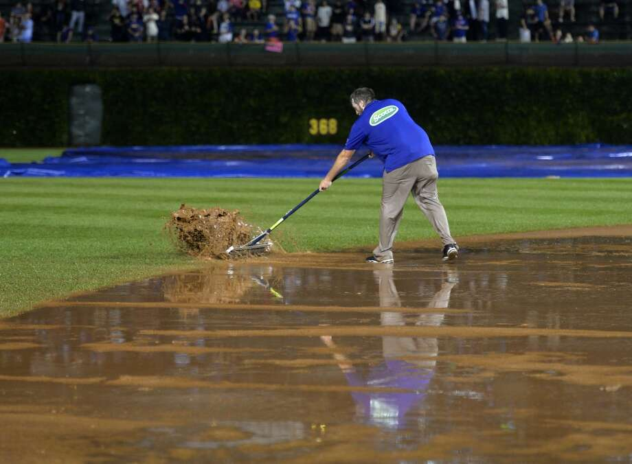 A member of the grounds crew uses a roller to remove water from the infield after a torrential downpour stopped play during the fifth inning. Photo: Brian Kersey, Getty Images