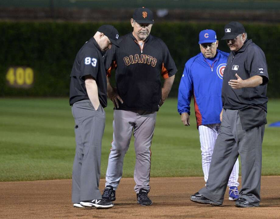 Managers Bruce Bochy and Rick Renteria discuss the condition of the field with the umpires Will Little (left) and Hunter Wendelstedt (right) during a rain delay at Wrigley Field. Photo: Brian Kersey, Getty Images