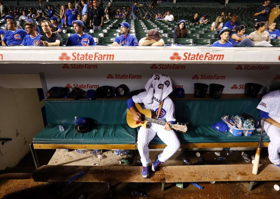 Chicago Cub backup catcher John Baker, center, plays his guitar during a rain delay. Photo: Jeff Haynes, Associated Press