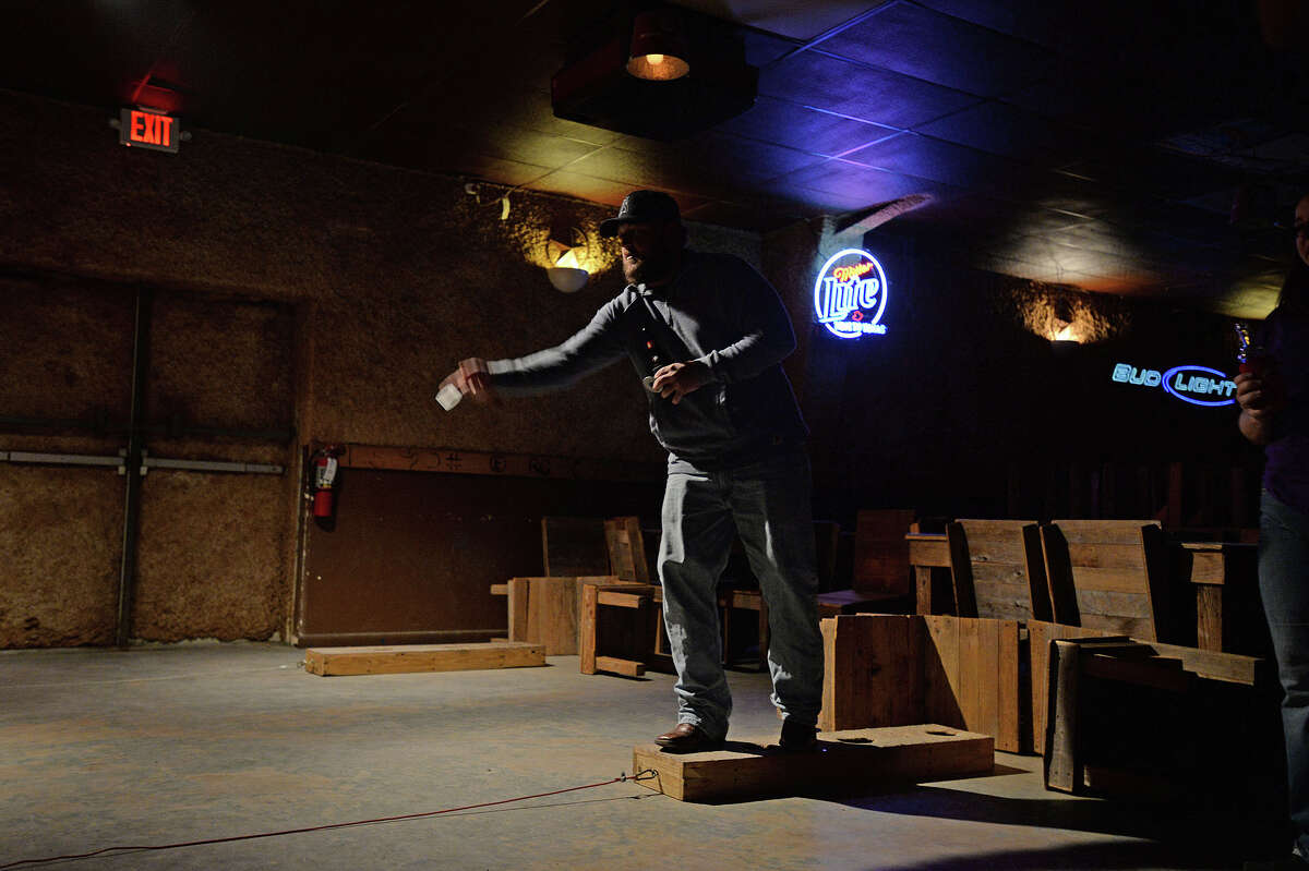 A person throws a washer during a game of washers at Honky Tonk Texas Thursday. Michael Rivera/@michaelrivera88