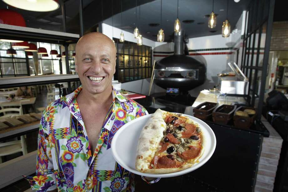 Andrea Magi holds the namesake dish the Mascalzone at Mascalzone, 12126 Westheimer,  Friday, Aug. 15, 2014, in Houston. The concoction is a half-pizza and half-calzone. Mascalzone was founded by retired Italian Olympic boxer Andrea Magi in London. ( Melissa Phillip / Houston Chronicle ) Photo: Melissa Phillip, Staff / © 2014  Houston Chronicle