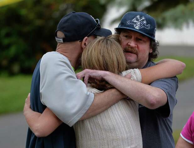 A woman is comforted by friends at the scene of double homicide at 709 First Ave. Wednesday morning, Aug. 20, 2014, in Troy, N.Y. (Skip Dickstein/Times Union) Photo: SKIP DICKSTEIN