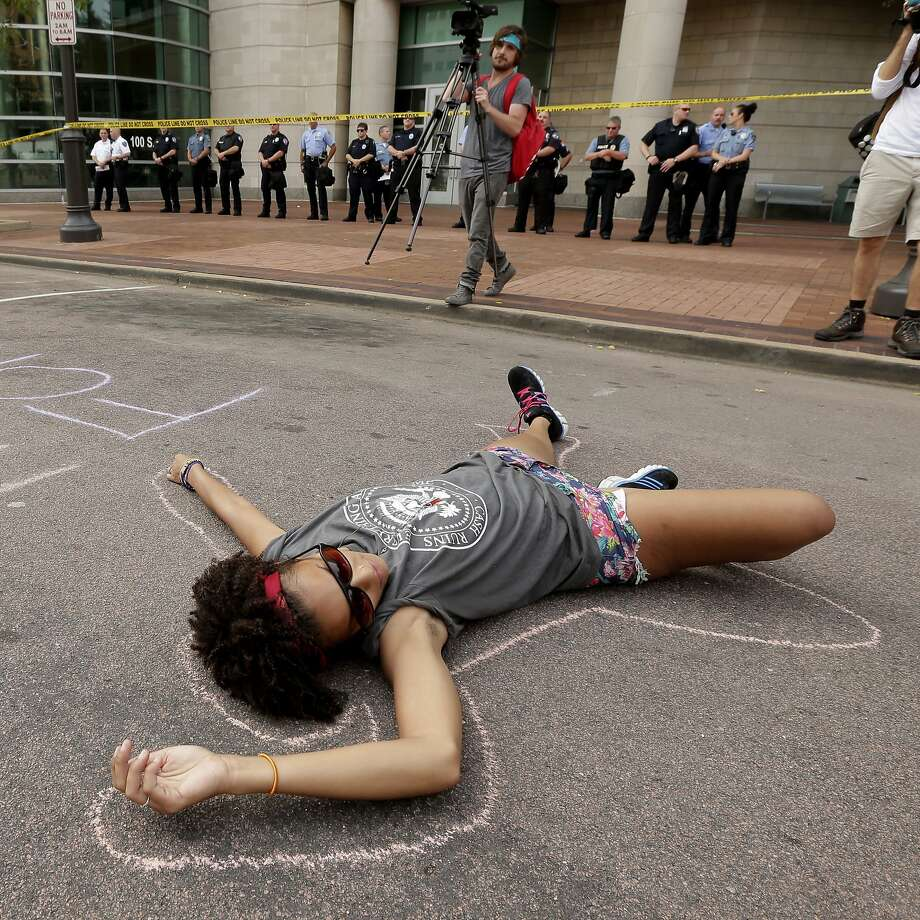 Mickey Iluebbey, from Minneapolis, lies in the street outside the Buzz Westfall Justice Center in Clayton, Mo., Wednesday, Aug. 20, 2014, where a grand jury is expected to convene to consider possible charges against the Ferguson, Mo. police officer who fatally shot 18-year-old Michael Brown. Brown's shooting in the middle of a street has sparked a more than week of protests, riots and looting in the St. Louis suburb.  Photo: Charlie Riedel, Associated Press