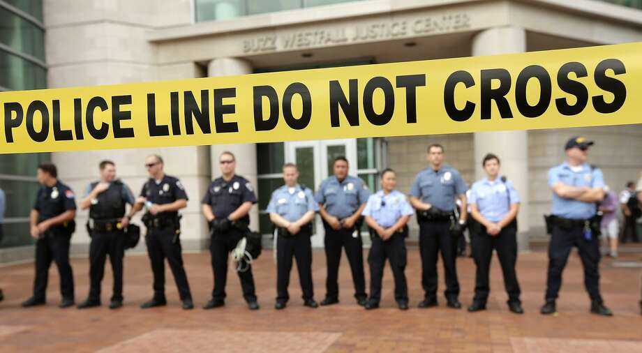Police guard the entrance to the Buzz Westfall Justice Center in Clayton, Mo., Wednesday, Aug. 20, 2014, where a grand jury is expected to convene to consider possible charges against the Ferguson, Mo. police officer who fatally shot 18-year-old Michael Brown. Brown's shooting in the middle of a street has sparked a more than week of protests, riots and looting in the St. Louis suburb. Photo: Charlie Riedel, Associated Press