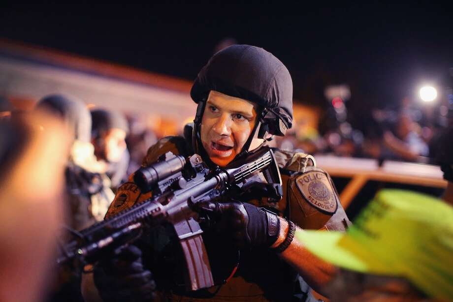 Police charge into the media work area with rifles at ready as they try to control demonstrators protesting the killing of teenager Michael Brown on August 19, 2014 in Ferguson, Missouri. Brown was shot and killed by a Ferguson police officer on August 9. Despite the Brown family's continued call for peaceful demonstrations, violent protests have erupted nearly every night in Ferguson since his death.  Photo: Scott Olson, Getty Images