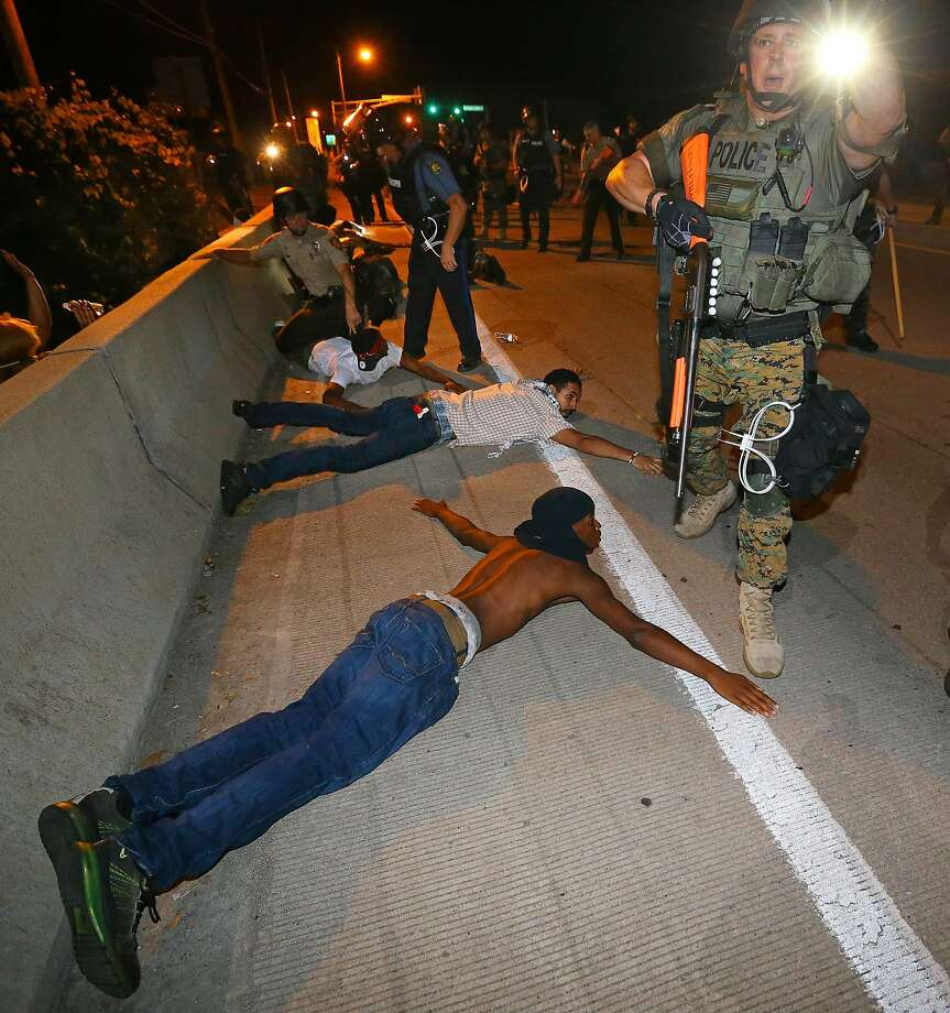 Police begin arresting dozens of protesters on West Florissant Avenue after they refused to leave the area and some began throwing objects at officers in Ferguson, Mo. early Wednesday, Aug. 20, 2014. On Aug. 9, 2014, a white police officer fatally shot Michael Brown, an unarmed black 18-year old, in the St. Louis suburb.  Photo: Curtis Compton, Associated Press
