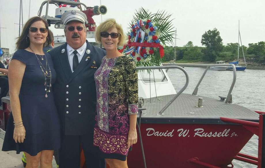 From left, Terese Flaherty, David W. Russell, III, and Eleanor Macfarlane, in front of the new fire boat named in honor of their father, former Fire Chief David W. Russell, Jr. Photo: Contributed Photo /  Fairfield Citizen contributed