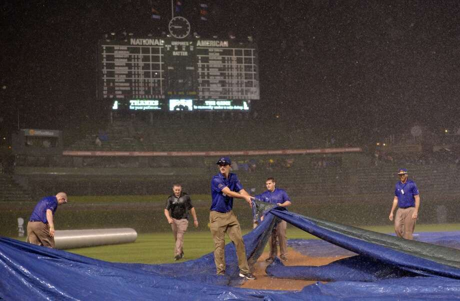 Chicago Cubs ground crew members struggle to get the tarp on the field as rain falls during the fifth inning of the Chicago Cubs game against the San Francisco Giants at Wrigley Field on August 19, 2014 in Chicago, Illinois Photo: Brian Kersey, Getty Images