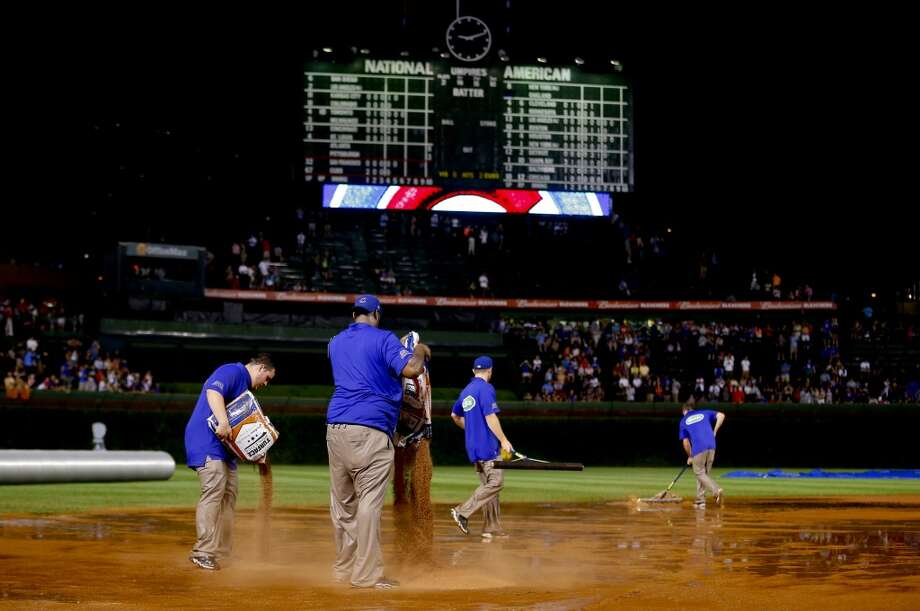 The grounds crew works on the field after a heavy rain soaked Wrigley Field during the fifth inning of a baseball game between the San Francisco Giants and the Chicago Cubs on Tuesday, Aug. 19, 2014, in Chicago. Photo: Jeff Haynes, Associated Press