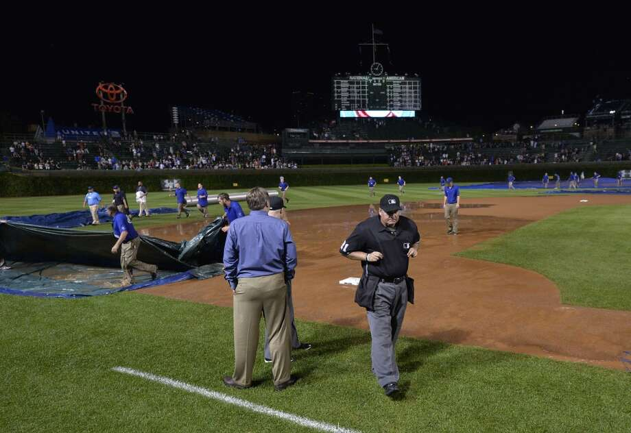 Home plate umpire Hunter Wendelstedt (center) inspects the field after a torrential downpour stopped play of the Chicago Cubs game against the San Francisco Giants during the fifth inning at Wrigley Field on August 19, 2014 in Chicago, Illinois. Photo: Brian Kersey, Getty Images