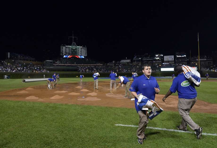 Grounds crew work on the field after heavy rains suspended play during the fifth inning of the Chicago Cubs game against the San Francisco Giants at Wrigley Field on August 19, 2014 in Chicago, Illinois. Photo: Brian Kersey, Getty Images