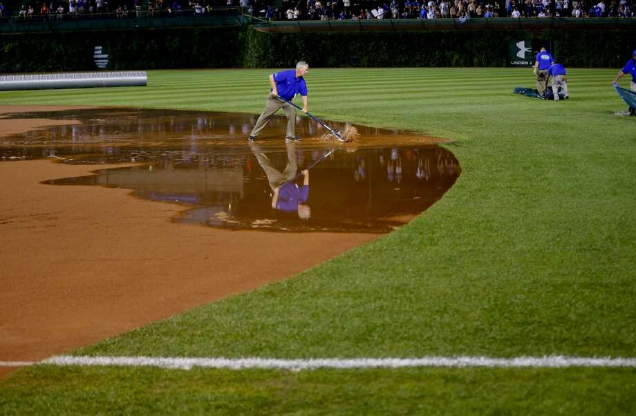 The grounds crew work on the field after a heavy rain soaked Wrigley Field during the fifth inning of a baseball game between the San Francisco Giants and the Chicago Cubs on Tuesday, Aug. 19, 2014, in Chicago. Photo: Jeff Haynes, Associated Press