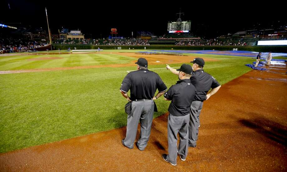 The umpires look over the field after a heavy rain soaked Wrigley Field during a baseball game between the San Francisco Giants and the Chicago Cubs in the fifth inning Tuesday, Aug. 19, 2014, in Chicago. Photo: Jeff Haynes, Associated Press