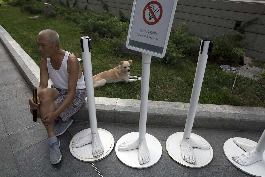 Smoking while barefoot absolutely prohibited:No-smoking signs in Beijing have feet. Photo: Ng Han Guan, Associated Press