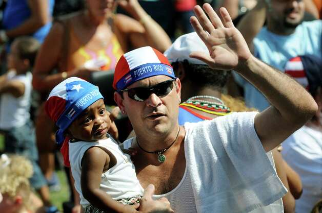 Puerto Rican native Pedro Millet of Amsterdam, center, dances with his grandson, Gabriele, 18 months, during the Albany Latin Fest on Saturday, Aug. 25, 2012, at Washington Park in Albany, N.Y. (Cindy Schultz / Times Union) Photo: Cindy Schultz / 00019020A