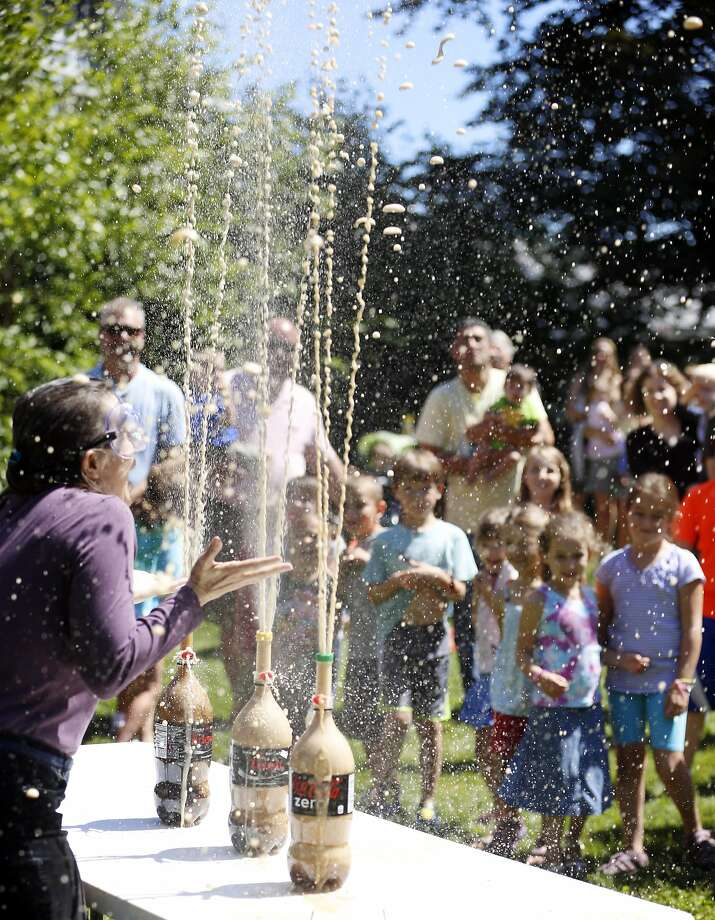 Hey, we were going to drink that:Lenox Library executive director Sharon Hawkes drops Mentos into bottles of Coke to reward summer readers for exceeding a goal of 500 reading hours this summer in Lenox, Mass. Photo: Stephanie Zollshan, Associated Press