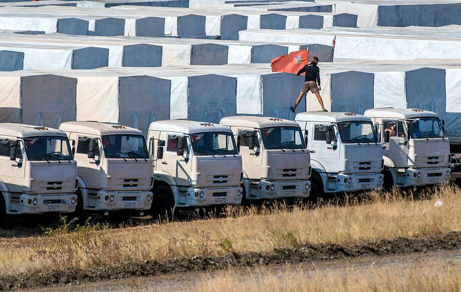 Noncombatant, don't shoot: A driver attaches a red flag to his truck, part of the Russian humanitarian convoy parked not far from a checkpoint at the Ukrainian border near Kamensk-Shakhtinsky. Photo: Dmitry Serebryakov, AFP/Getty Images