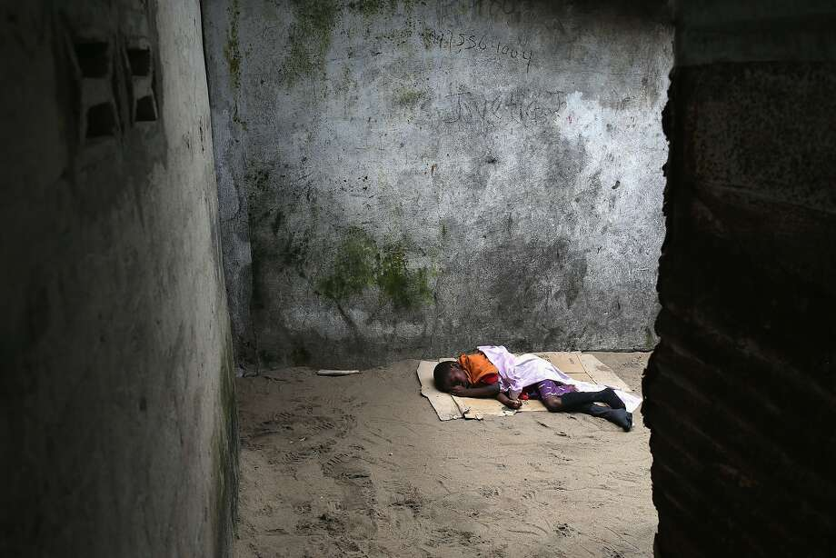 Sick and abandoned:Saah Exco, a very sick 10-year-old boy, lies in a back alley of the West Point slum in Monrovia, Liberia. Saah was one of the patients pulled out of a holding center for suspected Ebola patients when the facility was overrun by a mob. A local clinic refused to treat the boy, according to residents, because of the danger of infection. Photo: John Moore, Getty Images