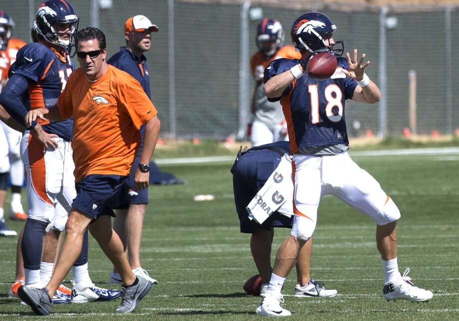 Broncos and former Houston Texans quarterbacks coach Greg Knapp, left, walks past quarterback Peyton Manning (18) and he throws a pass. Photo: Brett Coomer, Houston Chronicle