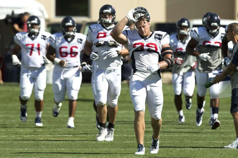 Texans defensive end J.J. Watt (99) takes off his helmet as he gets ready to stretch.