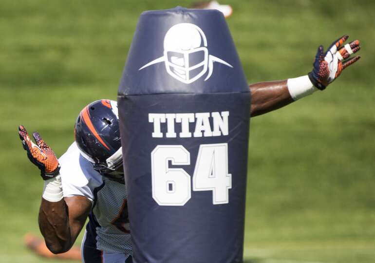 Broncos defensive end Kenny Anunike hits a blocking dummy.