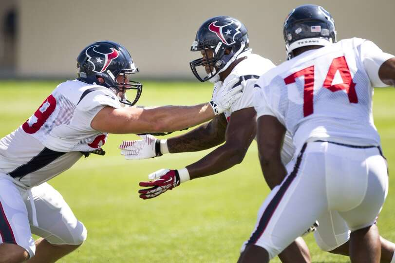 Texans defensive end J.J. Watt (99) runs a drill with defensive end Keith Browner (98) and defensive