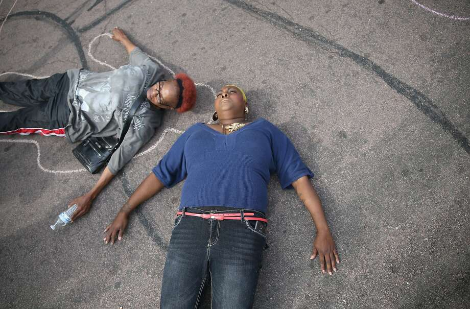 Protesters lay on the ground to draw lines around their bodies as they and other demonstrators protest outside of the Buzz Westfall Justice Center where a grand jury will begin looking at the circumstances surrounding the fatal police shooting of an unarmed teenager Michael Brown on August 20, 2014 in Clayton, Missouri. Brown was shot and killed by a Ferguson, Missouri police officer on August 9. Despite the Brown family's continued call for peaceful demonstrations, violent protests have erupted nearly every night in Ferguson since his death  Photo: Joe Raedle, Getty Images