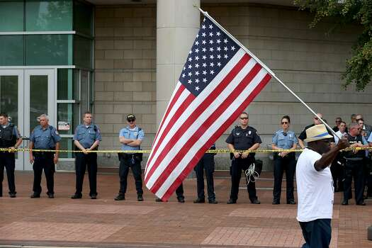Police stand guard outside the entrance as demonstrators protest outside of the Buzz Westfall Justice Center where a grand jury will begin looking at the circumstances surrounding the fatal police shooting of an unarmed teenager Michael Brown on August 20, 2014 in Clayton, Missouri. Brown was shot and killed by a Ferguson, Missouri police officer on August 9. Despite the Brown family's continued call for peaceful demonstrations, violent protests have erupted nearly every night in Ferguson since his death  Photo: Joe Raedle, Getty Images