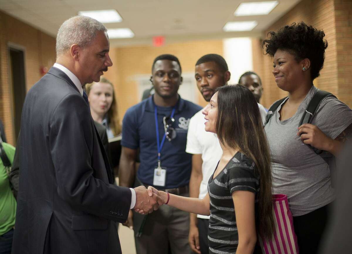Attorney General Eric Holder shakes hands with Bri Ehsan, 25, right, following his meeting with students at St. Louis Community College Florissant Valley in Ferguson, Mo., Wednesday, Aug. 20, 2014. Holder arrived in Missouri on Wednesday, a small group of protesters gathered outside the building where a grand jury could begin hearing evidence to determine whether a Ferguson police officer who shot 18-year-old Michael Brown should be charged in his death. (AP Photo/Pablo Martinez Monsivais/Pool)