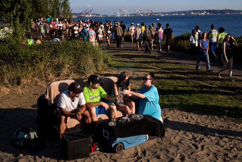 From left, Tommy Tompson and Jake Rossi, owners of Jettrays, share their bong with Darci Board and Desiree Dell from their seat on a portable, inflatable couch with a view of Mount Rainier in the background on the final day of Hempfest, Seattle's annual gathering to advocate the decriminalization of marijuana, photographed Sunday, August 17, 2014, at Myrtle Edwards Park on the Seattle waterfront in Seattle, Washington. The three-day annual event includes political rallies, concerts, and an arts and crafts fair. (Jordan Stead, seattlepi.com) Photo: JORDAN STEAD, SEATTLEPI.COM