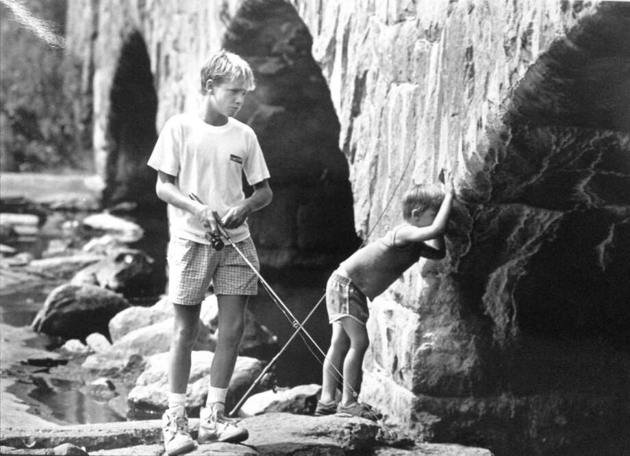 Two boys, Christian Izzo, 14, and his cousin, Wayne Hemingway, 5, test their fishing skills under Darien's Ring's End Road Bridge on Aug. 23, 1989. Photo: File Photo / Stamford Advocate File Photo