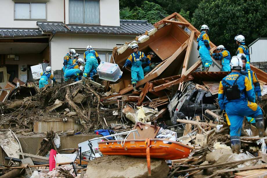 Police officers search for missing people after a landslide hit a residential area in the western city of Hiroshima. Landslides are a constant risk in mountainous, crowded Japan. Photo: Jiji Press, AFP/Getty Images
