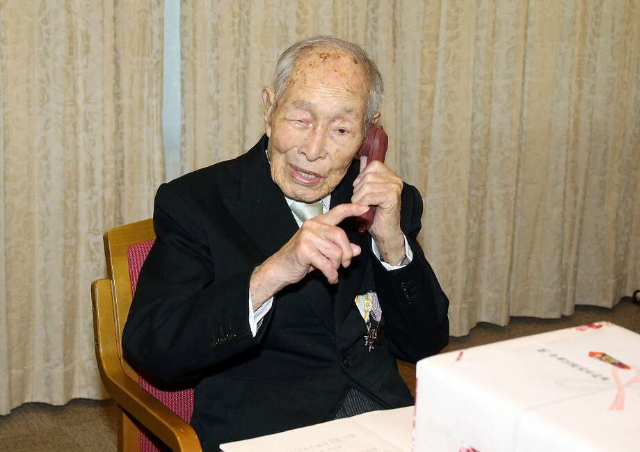 Sakari Momoi uses a phone at a Tokyo hospital. He was born before the Wright brothers carried out the first human flight. Photo: Japan Pool, AFP/Getty Images