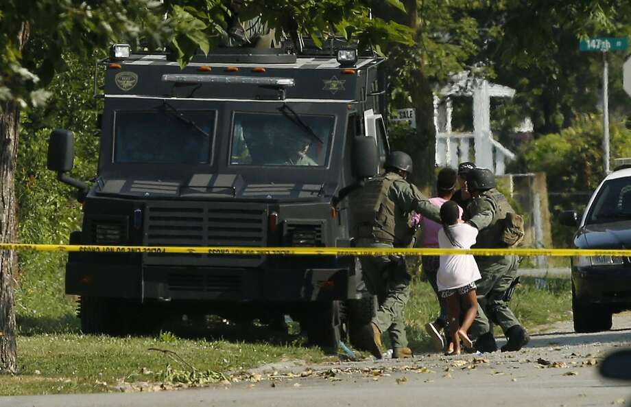 Police units stormed a Harvey, Ill., home, saving two women and two children and arresting two suspects, ending a drawn-out hostage situation. Photo: Jose Osorio, McClatchy-Tribune News Service