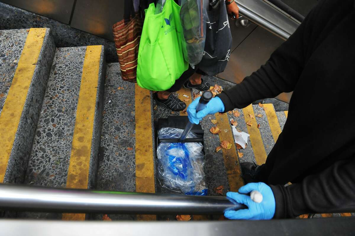 A commuter passes a BART service worker cleaning the steps of one of the entrances to the Civic Center BART station on August 20, 2014 in San Francisco, CA.