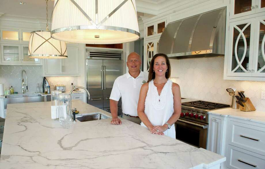 Contractor Vincent Sciarretta, left, and Hillary Miller, right, pose for a photo in the kitchen of Miller's Darien home on Tuesday, August 19, 2014. Photo: Lindsay Perry / Stamford Advocate